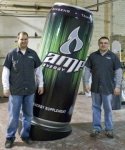 Travis Cantwell (left) and Todd Randall of Elite Signs & Graphix stand next to the 7-foot tall Amp can, the trademark energy drink of Pepsi Co., that they helped Signs By Benchmark produce for the 2009 ISA show.